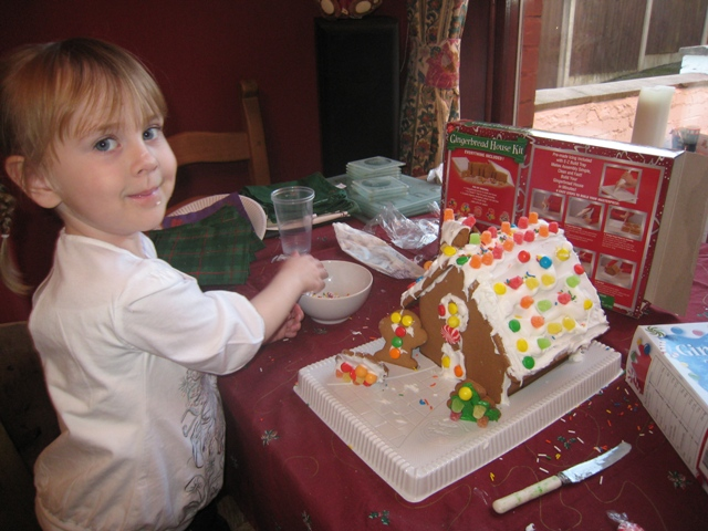 Olivia proudly shows off her gingerbread house
