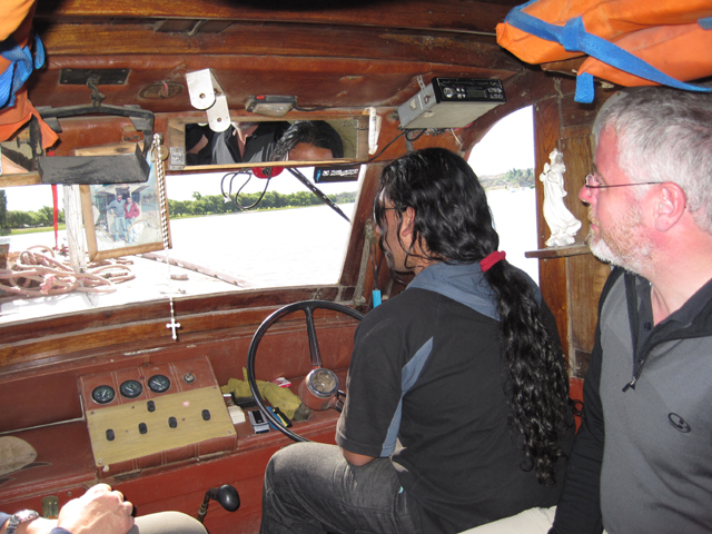 Inside the ferry, Simon watches intently in case the driver reaches for his prayer beads...